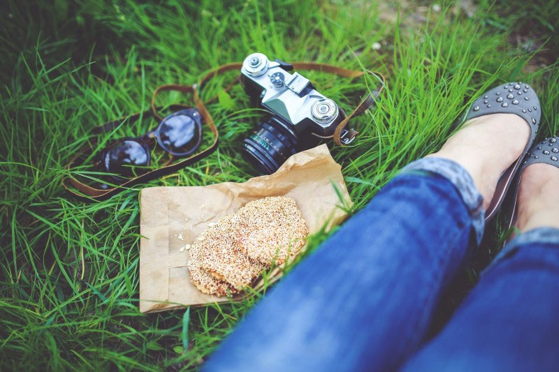 A woman resting in grass with camera and cookies